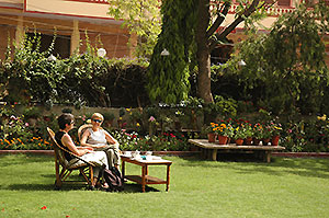 The front lawn of Jaipur Hotel Arya Niwas with many species of birds and trees where you can relax